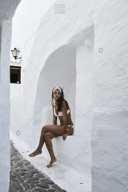 Spain- Menorca- young woman wearing white bikini sitting in a wall niche