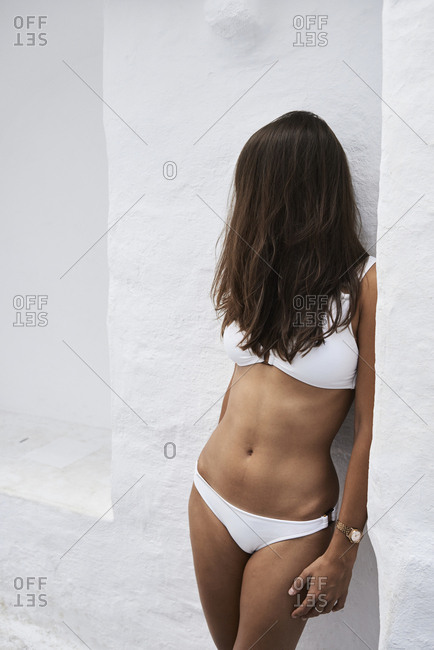 Hair covering face of young woman wearing white bikini