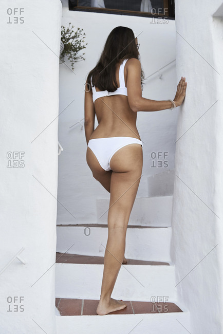 Back view of woman wearing white bikini walking upstairs