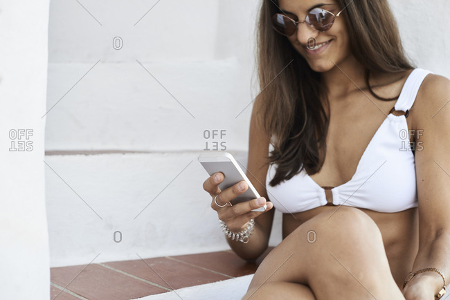 Smiling young woman wearing white bikini sitting on stairs using smartphone