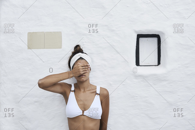Young woman wearing white bikini top leaning against white wall covering eyes with her hand