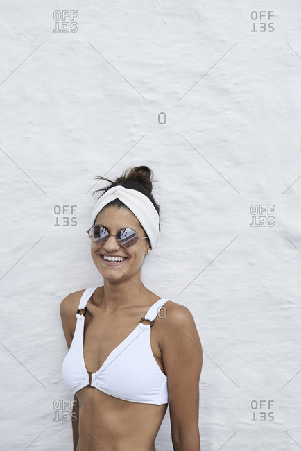 Portrait of laughing young woman wearing white bikini top leaning against white wall