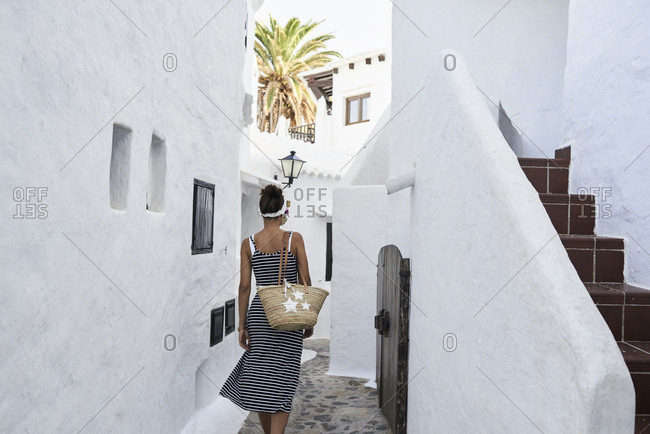 Spain- Menorca- Binibequer- back view of woman walking in an alley