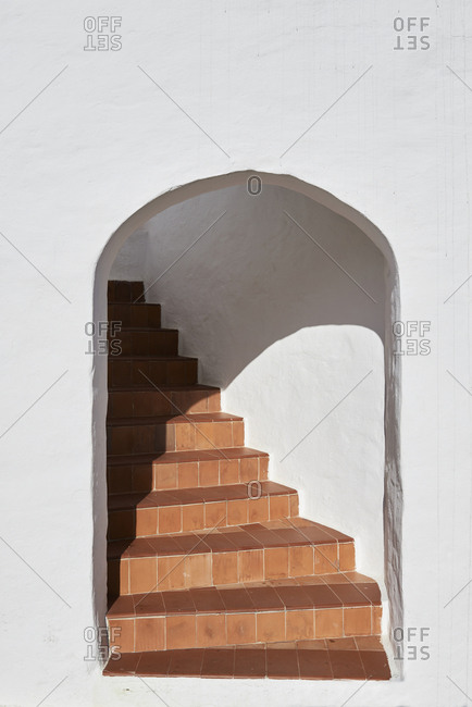 Spain- Menorca- white wall with arch and staircase behind