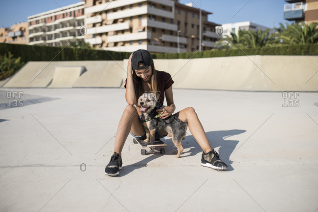 Young woman sitting on skateboard- stroking her dog