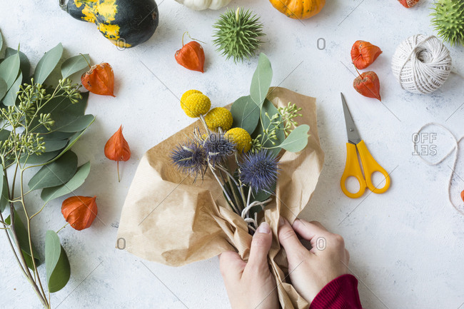 Autumnal decoration- ornamental pumpkins- hands wrapping bunch of flowers