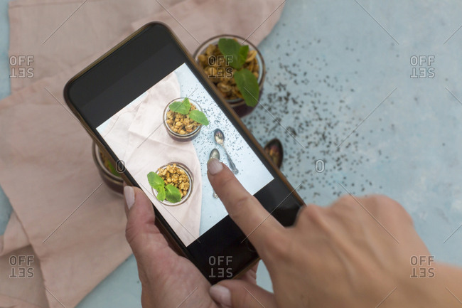 Woman's hand taking photo of dessert with smartphone- close-up
