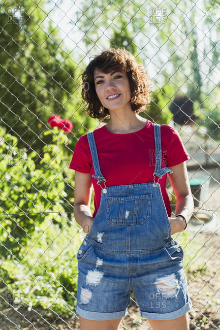 Portrait of smiling woman wearing jeans dungarees