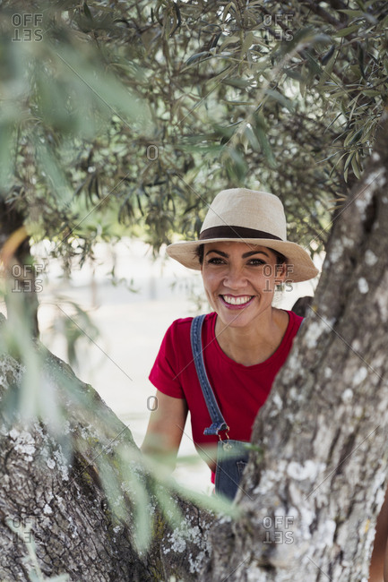 Portrait of smiling woman behind olive tree