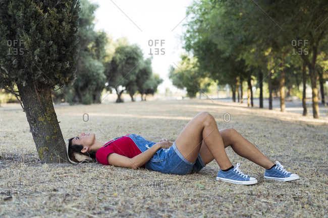 Woman lying on ground in nature looking up