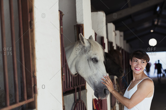 Portrait of happy woman stroking horse in stable