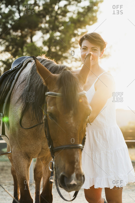 Portrait of smiling woman standing besides riding horse at backlight