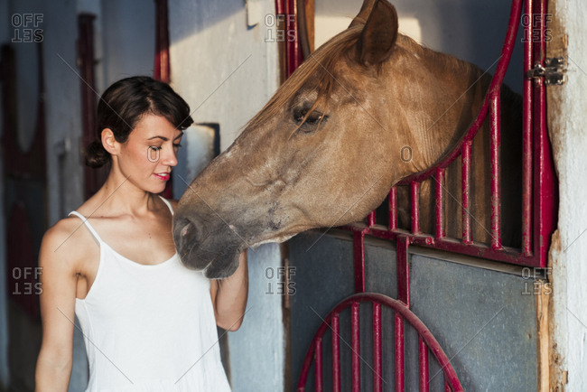 Portrait of woman stroking horse in stable