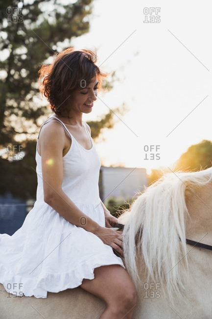 Smiling woman in white dress riding bareback on horse at sunset