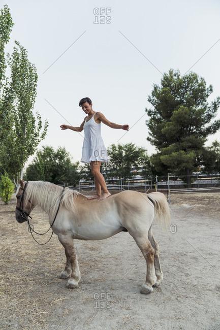 Smiling woman balancing barefoot on horseback