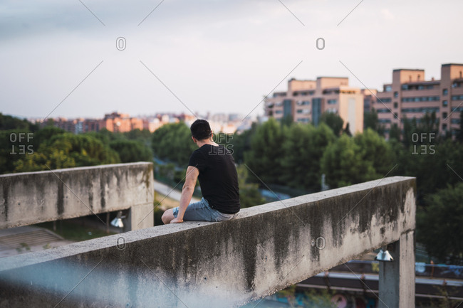 Back view of man sitting on a wall enjoying view at evening light