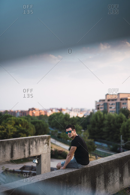 Portrait of man relaxing on a wall at evening