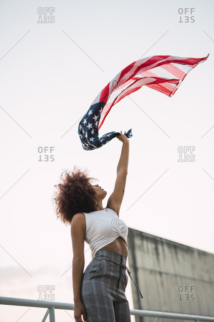 Young woman swinging American flag