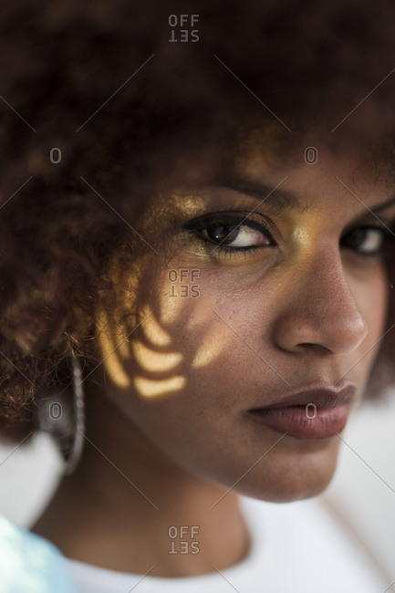 Portrait of young woman with flare on her cheek