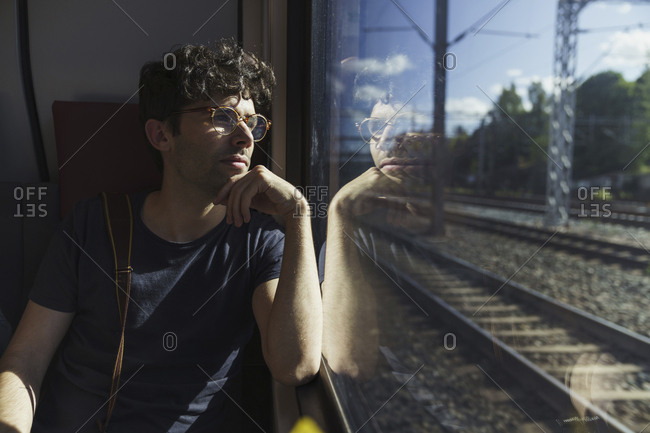 Man traveling by train looking out of window