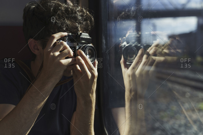 Man traveling by train taking picture with old-fashioned camera