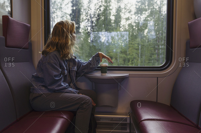 Woman traveling by train looking out of window