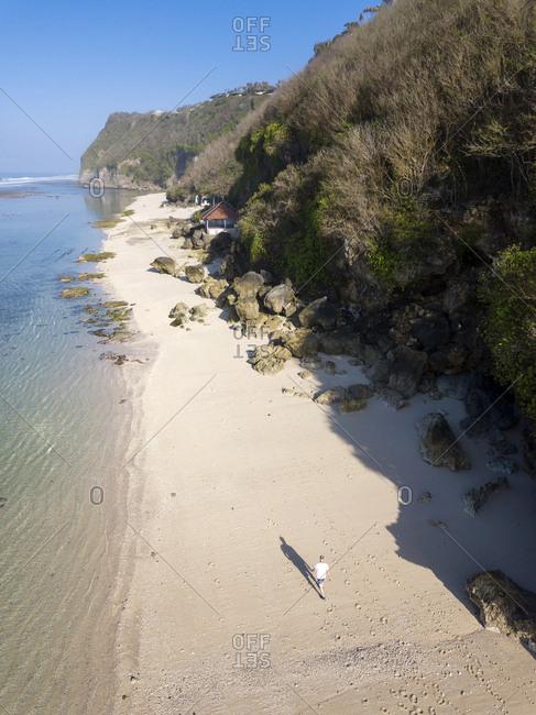 Indonesia- Bali- Aerial view of Karma Kandara beach- man walking on beach