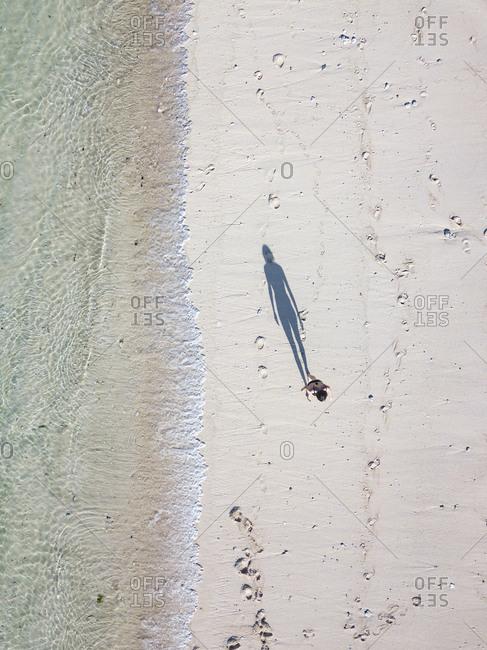Indonesia- Bali- Aerial view of Karma Kandara beach- woman standing on the beach