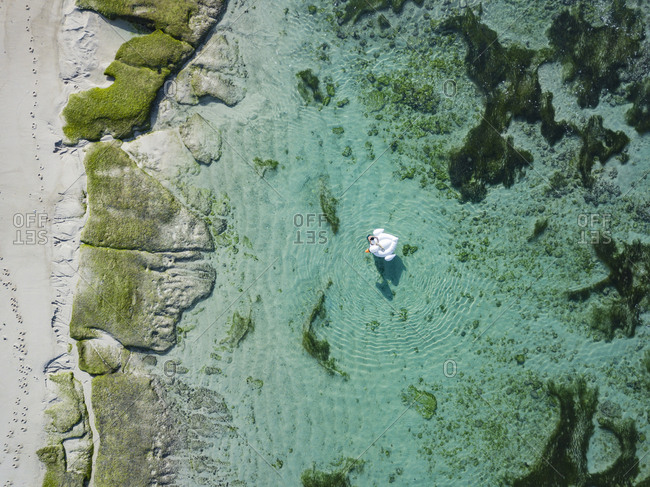 Indonesia- Bali- Aerial view of Karma Kandara beach- one woman- airbed floating on water