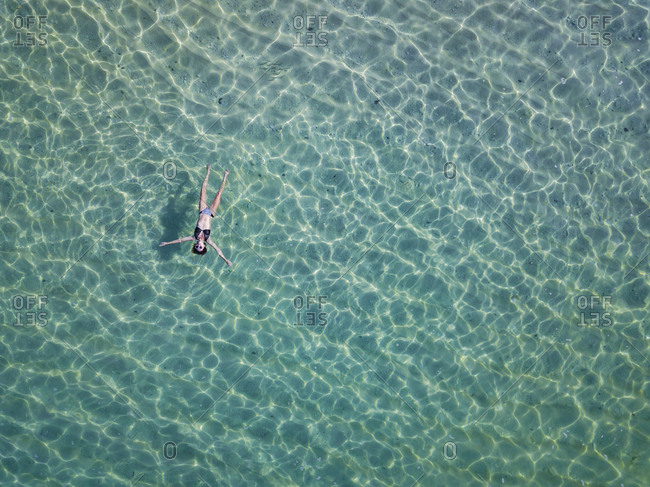 Indonesia- Bali- Melasti- Aerial view of Karma Kandara beach- woman floating on water