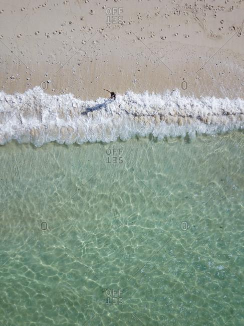 Indonesia- Bali- Melasti- Aerial view of Karma Kandara beach- woman going into water