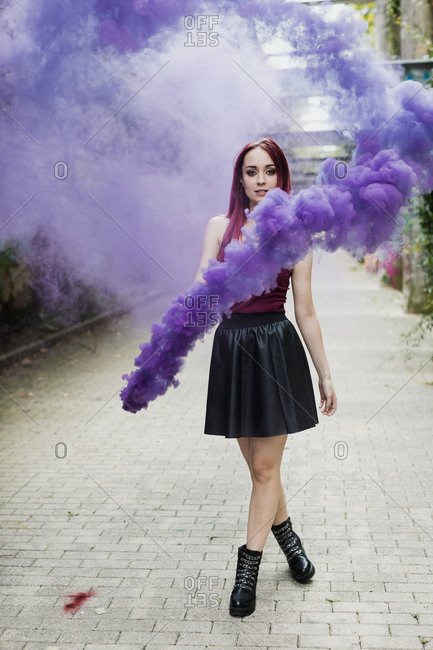 Young woman holding smoke torch outdoors