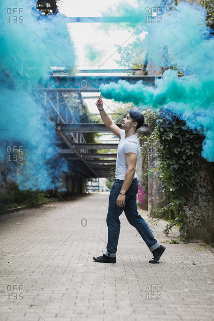 Young man walking with smoke torch outdoors