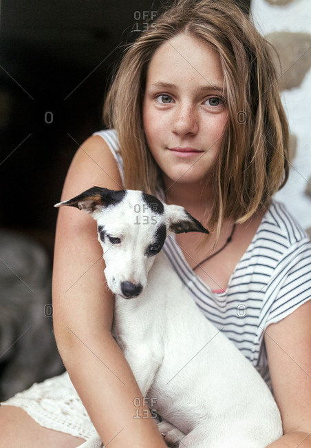 Portrait of freckled girl with puppy on her lap