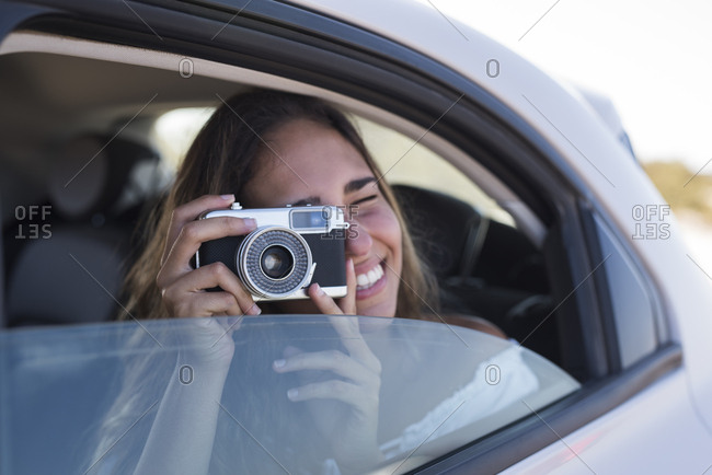 Woman sitting in car- taking pictures with a camera
