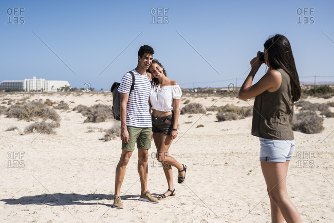 Young woman taking pictures of a young couple on the beach