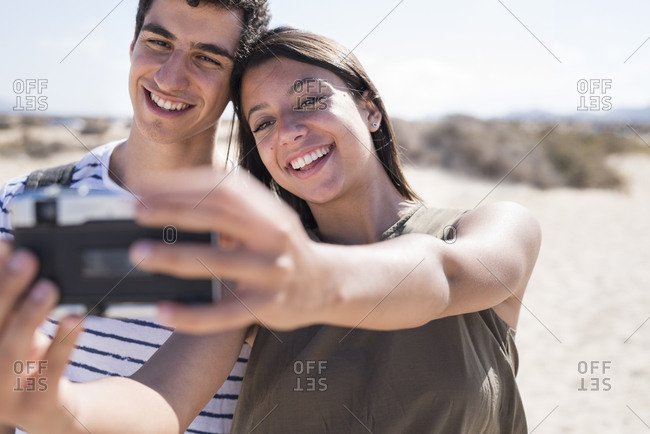 Young couple having fun on the beach- taking smartphone selfies