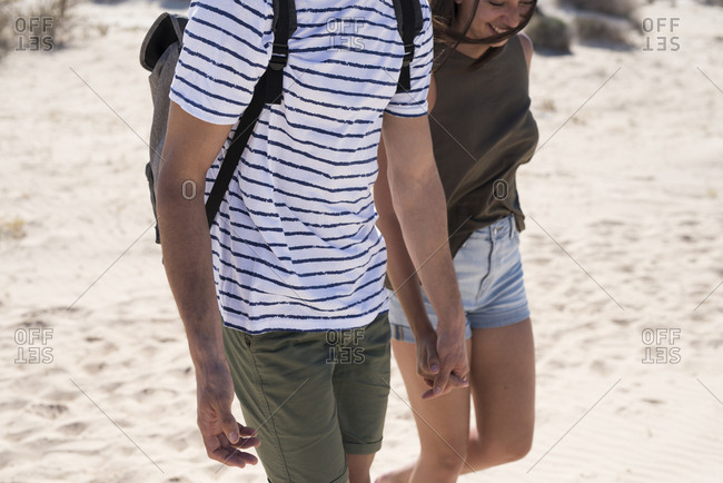 Young couple walking on the beach- holding hands
