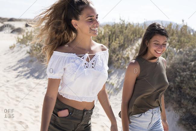 Friends walking on the beach- talking