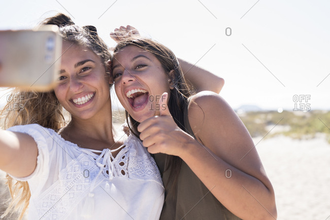 Girlfriends having fun on the beach- taking smartphone selfies