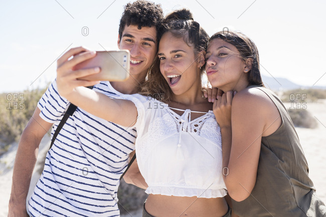 Friends having fun on the beach- taking smartphone selfies
