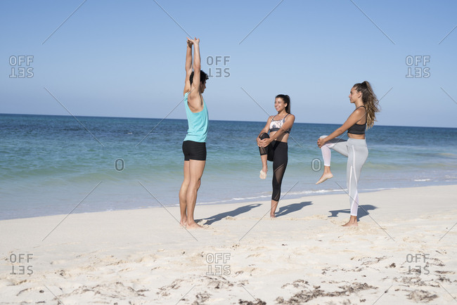Spain- Canary Islands- Fuerteventura- two young women and young man exercising on the beach