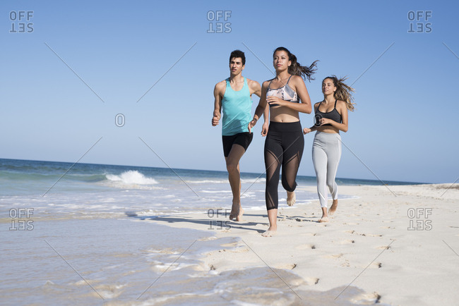 Spain- Canary Islands- Fuerteventura- two young women and young man running on the beach