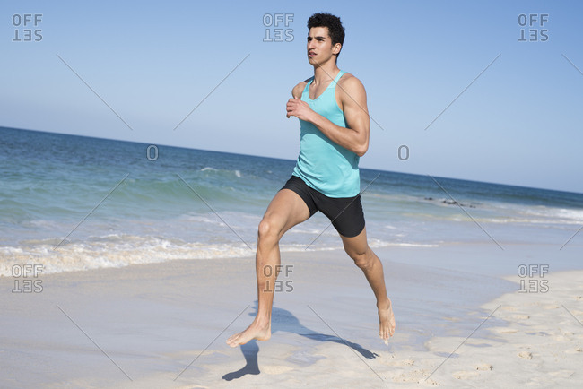 Spain- Canary Islands- Fuerteventura- young man running on the beach