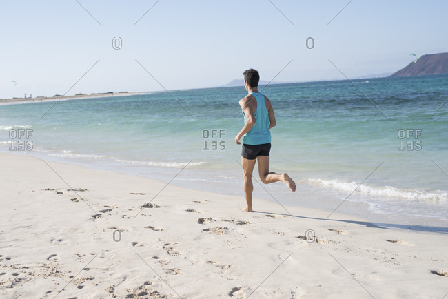 Spain- Canary Islands- Fuerteventura- rear view of young man running on the beach