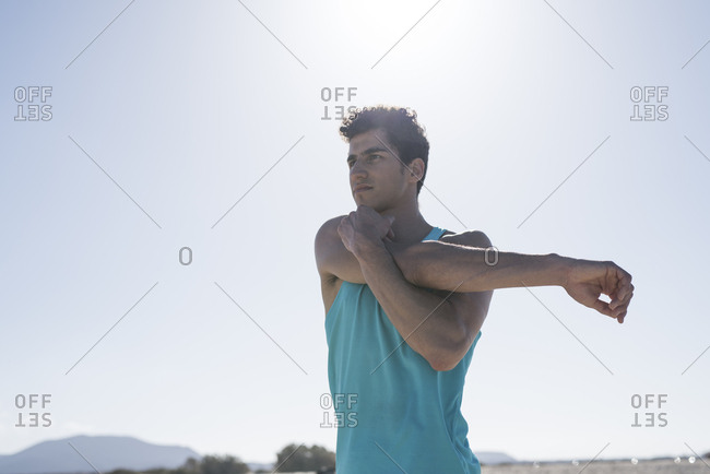 Spain- Canary Islands- Fuerteventura- young man stretching his arm under blue sky