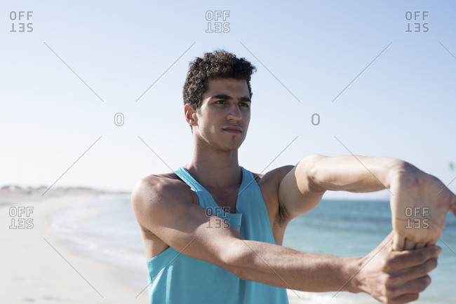 Spain- Canary Islands- Fuerteventura- young man stretching his arm on the beach