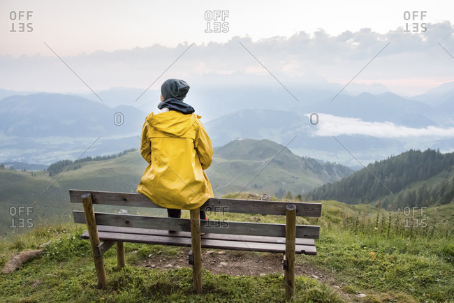 Austria- Tyrol- Fieberbrunn- Wildseeloder- woman sitting on bench with view on mountainscape