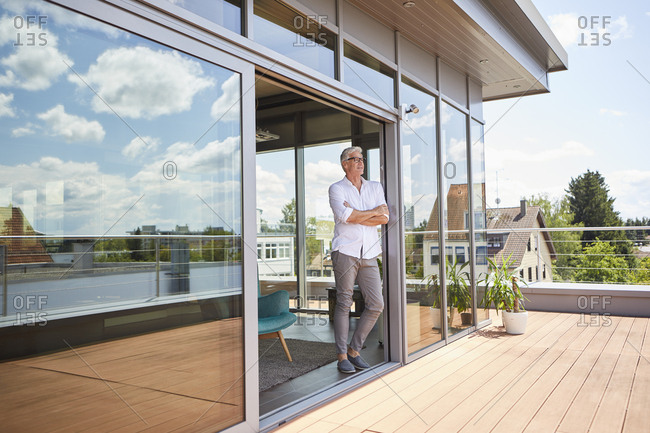 Mature man relaxing standing at roof terrace at home