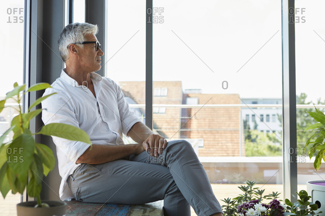 Pensive mature man sitting at the window at home